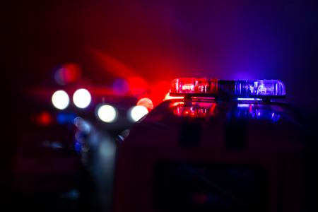 Coches de policía por la noche. Coche de policía persiguiendo un coche por la noche con fondo de niebla. 911 Coche de policía de respuesta de emergencia que se dirige a toda velocidad a la escena del crimen. Enfoque selectivo
