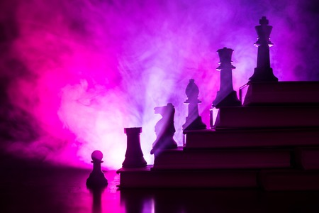 Gerarchia aziendale. Concetto di strategia con pezzi degli scacchi. Scacchi in piedi su una piramide di libri con il re in alto. Sfondo nebbioso scuro con luce tonica. Copia spazio. Archivio Fotografico
