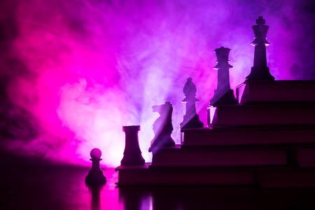 Jerarquía empresarial. Concepto de estrategia con piezas de ajedrez. Ajedrez de pie sobre una pirámide de libros con el rey en la parte superior. Fondo de niebla oscura con tonos de luz. Copie el espacio. Foto de archivo
