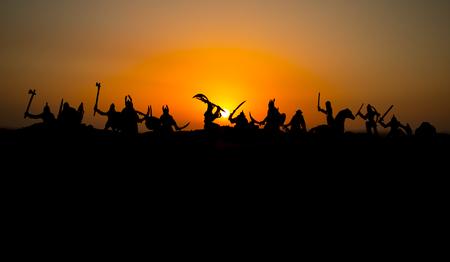 Escena de batalla medieval con caballería e infantería. Siluetas de figuras como objetos separados, lucha entre guerreros en el fondo de niebla al atardecer. Enfoque selectivo