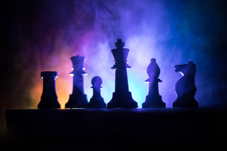 Chess board game concept of business ideas and competition or strategy ideas concept. Chess figures on a dark toned foggy background. Selective focus