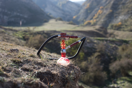 Hookah, traditional arabic waterpipe, direct sunset light, outdoor photo. Mountain background. Outdoor. Empty space.