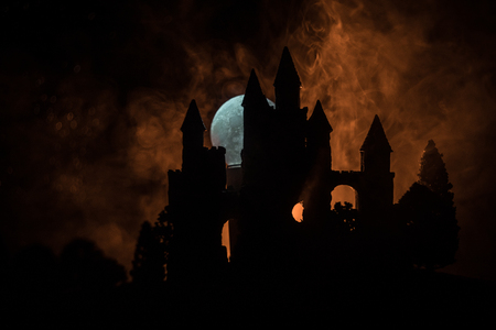 Mysterious medieval castle in a misty full moon. Abandoned gothic style old castle at night. Selective focus Stock Photo