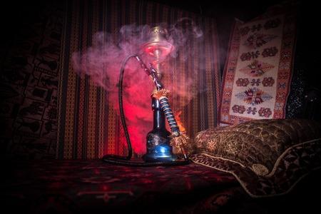 Hookah hot coals on shisha bowl making clouds of steam at Arabian interior. Oriental ornament on the carpet. Stylish oriental shisha in dark with backlight. For Shisha advertisement. Selective focus