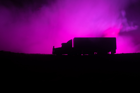 Big truck wagon rides on the road outside the city at night with foggy background. Decoration. Selective focus