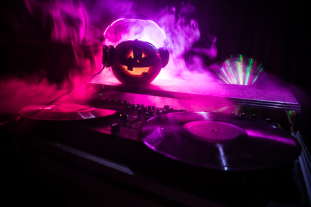 Halloween pumpkin on a dj table with headphones on dark background with copy space. Happy Halloween festival decorations and music concept. Empty space. Selective focus Stock Photo