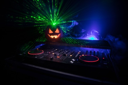 Halloween pumpkin on a dj table with headphones on dark background with copy space. Happy Halloween festival decorations and music concept. Empty space. Selective focus Imagens