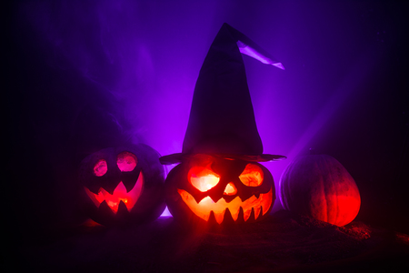 Group of Halloween Jack o Lanterns at night with a rustic dark foggy toned background. Selective focus 写真素材