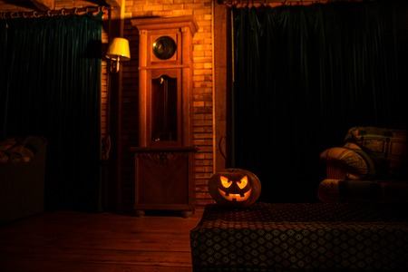 Halloween. Vintage interior in western style. Horror pumpkin with antique clock on background. Selective focus Stock Photo