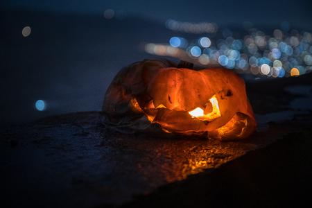Horror Halloween concept. Close up view of scary dead Halloween pumpkin glowing at dark background. Rotten pumpkin head. Selective focus