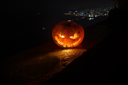 Horror Halloween concept. Close up view of scary dead Halloween pumpkin glowing at dark background. Selective focus Stock Photo