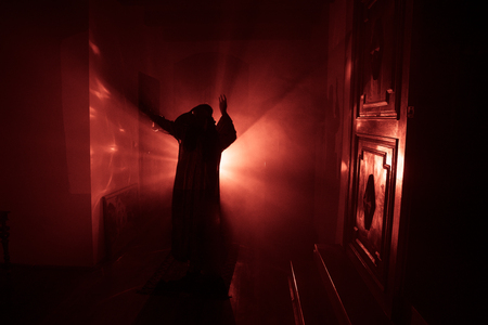 Horror silhouette of ghost inside dark room with mirror. Scary halloween concept. Silhouette of witch inside haunted house with fog and light on background. Selective focus