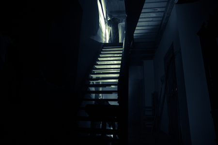 Inside of old creepy abandoned mansion. Silhouette of horror ghost standing on castle stairs to the basement. Spooky dungeon stone stairs in old castle with light. Horror Halloween concept Stock Photo