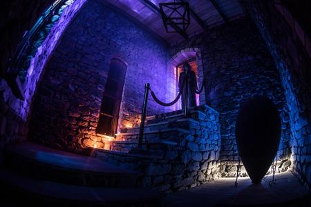 Innerhalb eines alten gruseligen verlassenen Herrenhauses. Silhouette des Horrorgeistes, der auf der Schlosstreppe zum Keller steht. Gespenstische Kerkertreppe im alten Schloss mit Licht. Horror-Halloween-Konzept