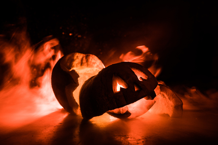 Horror Halloween concept. Close up view of scary dead Halloween pumpkin glowing at dark background. Destroyed pumpkin. Selective focus Stock Photo