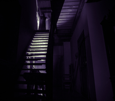 Inside of old creepy abandoned mansion. Silhouette of horror ghost standing on castle stairs to the basement. Spooky dungeon stone stairs in old castle with light. Horror Halloween concept Stok Fotoğraf