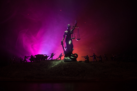 War - no justice concept. Military silhouettes fighting scene and The Statue of Justice on a dark toned foggy background. Selective focus