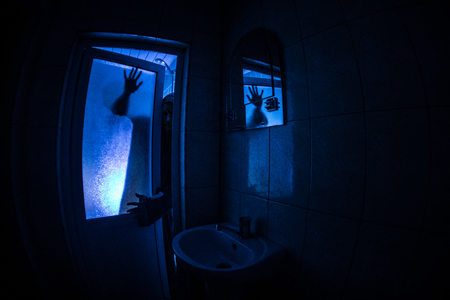 Horror silhouette of woman in window. Scary halloween concept Blurred silhouette of witch in bathroom Stockfoto