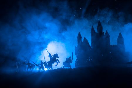Escena de batalla medieval con caballería e infantería. Siluetas de figuras como objetos separados, lucha entre guerreros sobre fondo brumoso en tonos oscuros con castillo medieval. Enfoque selectivo