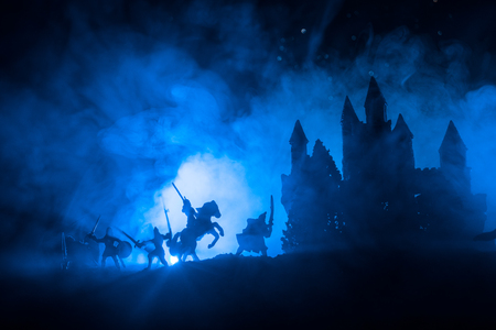 Mittelalterliche Kampfszene mit Kavallerie und Infanterie. Silhouetten von Figuren als separate Objekte, Kampf zwischen Kriegern auf dunkel getöntem nebligen Hintergrund mit mittelalterlicher Burg. Selektiver Fokus