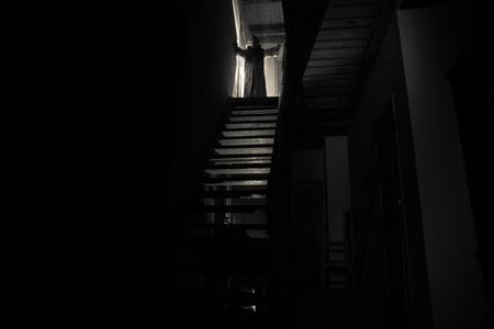 Innerhalb eines alten gruseligen verlassenen Herrenhauses. Silhouette des Horrorgeistes, der auf der Schlosstreppe zum Keller steht. Gespenstische Kerkertreppe im alten Schloss mit Licht. Horror-Halloween-Konzept Standard-Bild