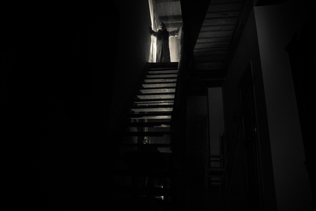 Inside of old creepy abandoned mansion. Silhouette of horror ghost standing on castle stairs to the basement. Spooky dungeon stone stairs in old castle with light. Horror Halloween concept 免版税图像