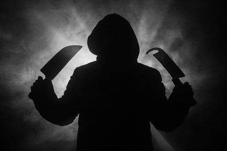Un dangereux homme cagoulé debout dans le noir et tenant de gros couteaux. Le visage ne peut pas être vu. Commettre un concept de crime