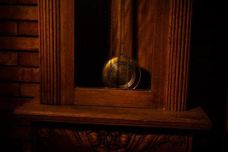 Vintage interior in western style. Big wooden antique clock with pendulum. Selective focus. Stock Photo