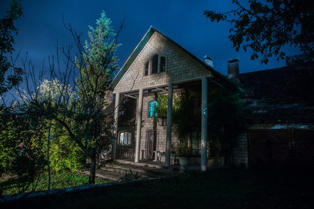 Mountain night landscape of building at forest at night with moon or vintage country house at night with clouds and stars. Summer night. Photo taken with long exposure 免版税图像
