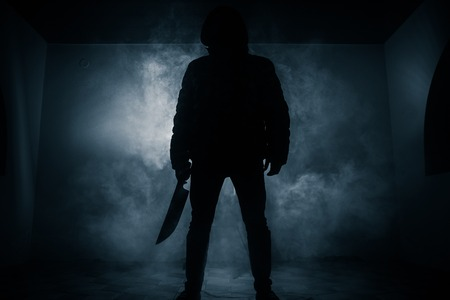 A dangerous hooded man standing in the dark and holding a knife. Face can not be seen. Committing a crime concept Stock Photo