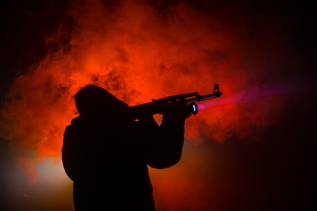 Silhouette of man with assault rifle ready to attack on dark toned foggy background or dangerous bandit holding gun in hand. Shooting terrorist with weapon theme decor