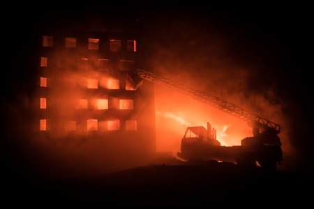 extinguish the fire of a private house at night. Toy fire truck with long ladder and burning building at night. Fire alarm concept. Selective focus Stockfoto