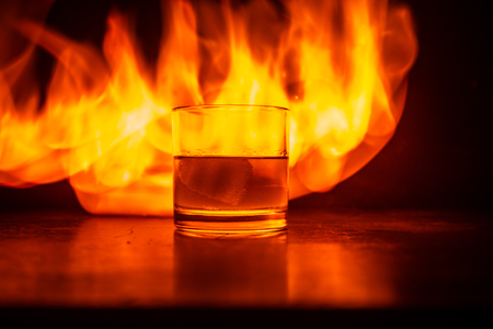 Whiskey in fire concept. Glass of whiskey and ice on wooden surface with color light and fog on background. Close up. Selective focus 스톡 콘텐츠