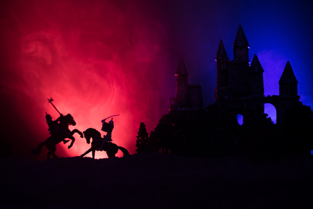 Medieval battle scene with cavalry and infantry. Silhouettes of figures as separate objects, fight between warriors on dark toned foggy background with old gothic castle