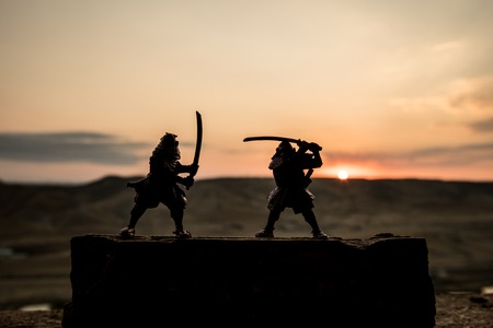 Silhouette of two samurais in duel. Picture with two samurais and sunset sky. Selective focus Imagens