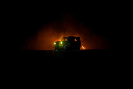 Off roader jeep silhouette on dark toned foggy sky background. Car with light at night. Selective focus 版權商用圖片