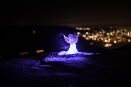 christmas angel on blur bokeh city lights at night on background. Little white guardian angel in snow. Christmas decoration