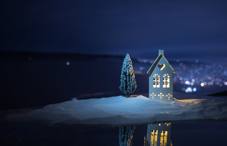 Christmas and New Year miniature house in the snow at night with fir tree. Little toy house on snow with tree and bokeh city lights on background. Christmas decorations. Holiday concept. 写真素材