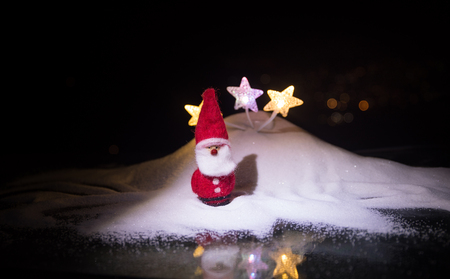 Abstract Winter background. Glowing stars in snow with small Santa Claus. New year Christmas concept Stock Photo