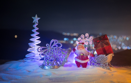 Christmas decorations. Fir tree standing on snow with beautiful holiday decorated background and traditional holiday attributes. Selective focus. Empty space for your text