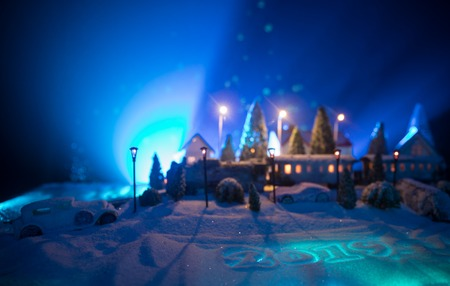 Miniature of winter scene with Christmas houses, train station, trees, covered in snow. Nights scene. New year or Christmas concept. Selective focus