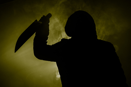 Un dangereux homme cagoulé debout dans le noir et tenant un couteau. Le visage ne peut pas être vu. Commettre un concept de crime Banque d'images