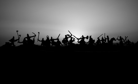 Medieval battle scene with cavalry and infantry. Silhouettes of figures as separate objects, fight between warriors on sunset foggy background. Selective focus 写真素材