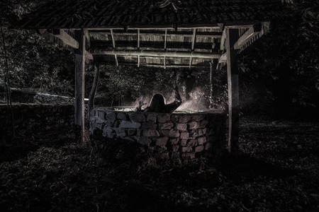 A terrible girl with long black hair is standing in a gloomy well. Scary Halloween photo. Dead zombie girl climbs out of the well