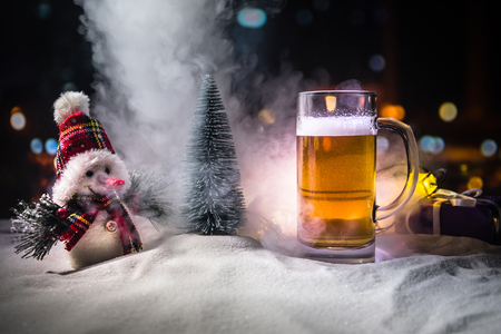 Mug of beer with Christmas decoration. Glass of light beer with foam in snow with creative New Year holiday artwork. Copy space Banque d'images - 113477909