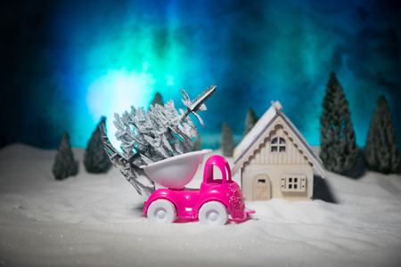 Toy car carrying a fir tree through the forest in winter Stock Photo