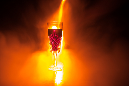 Wine glass in fire concept. One glass of red wine with burning fire on black background. Selective focus. Empty space 스톡 콘텐츠