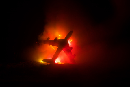 Air Crash. Burning falling plane. The plane crashed to the ground. Decorated with toy at dark fire background. Air accident concept. Selective focus 版權商用圖片