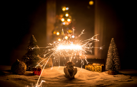 Glittering burning sparkler on snow with blurred Christmas tree on dark background. New Year Holiday concept with empty space for your text. Selective focus