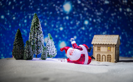 Festive background. Christmas decorations. Santa Claus (or Snowman) standing on snow with beautiful decorated background with holiday elements. Selective focus. Empty space for your text